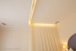 Moulures en staff, rideau voile motorisé, et plafond blanc mat dans la suite de l'hotel